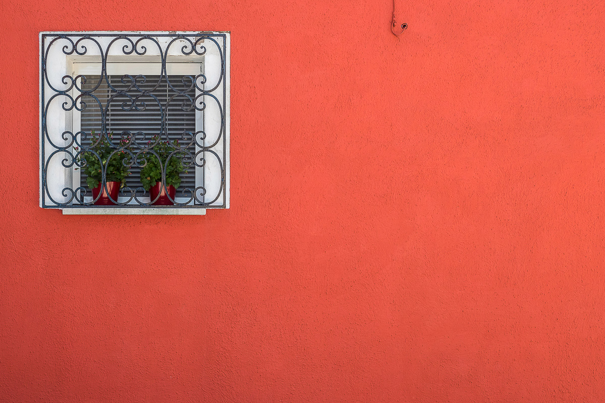 Detail of a red facade with a small window.