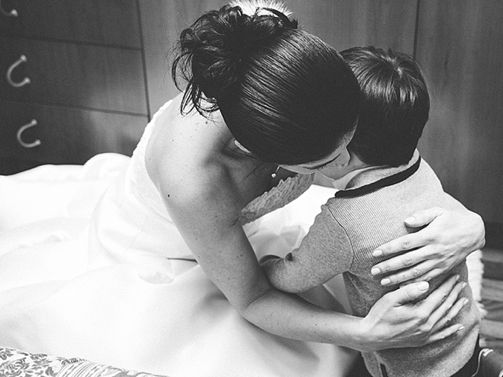 A black and white photo of a bride hugging her child.