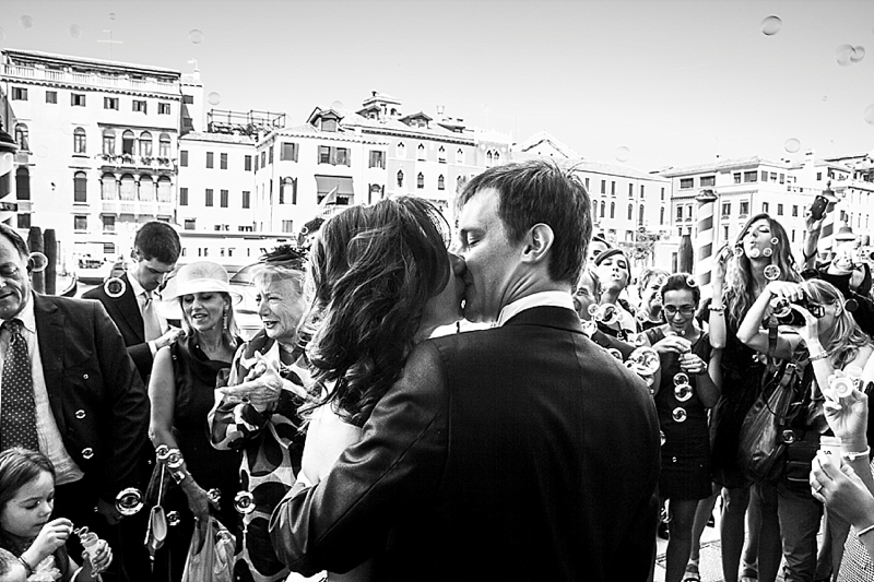 A black and white photo of a newly wed couple kissing in front of family and friends in Venice.