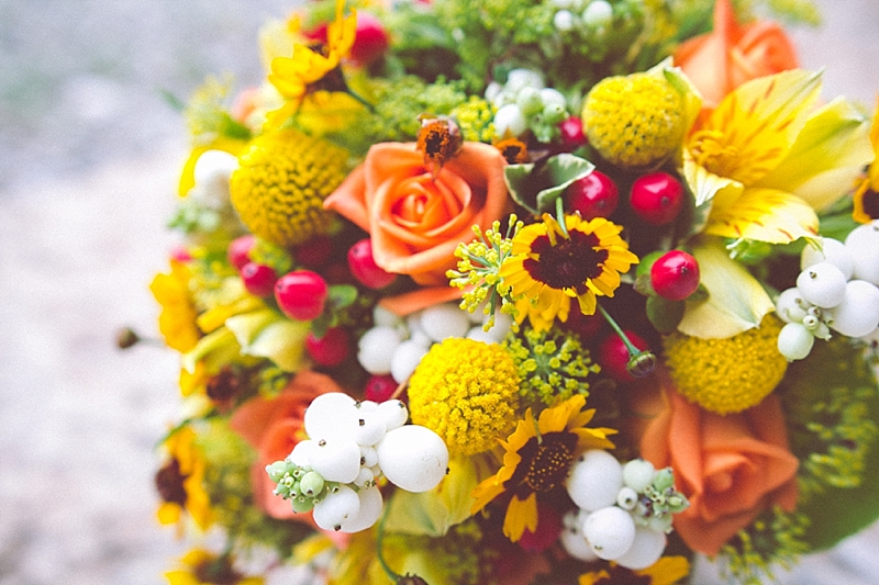 Photo of a wedding bouquet, made of yellow and orange flowers.