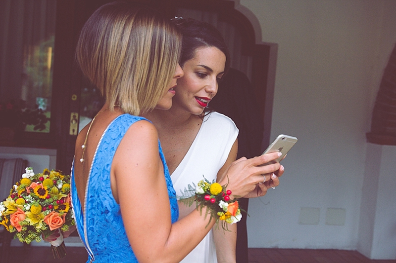 A candid photo of the bride and her bridesmaid taking a selfie
