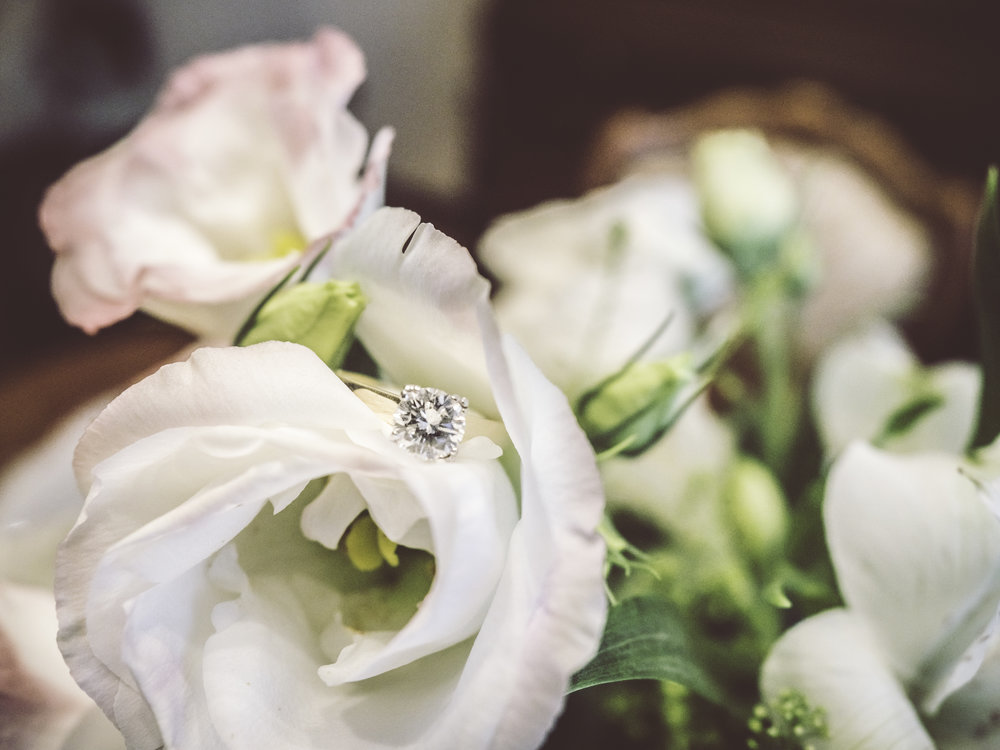 Photo of an engagement ring between flowers.