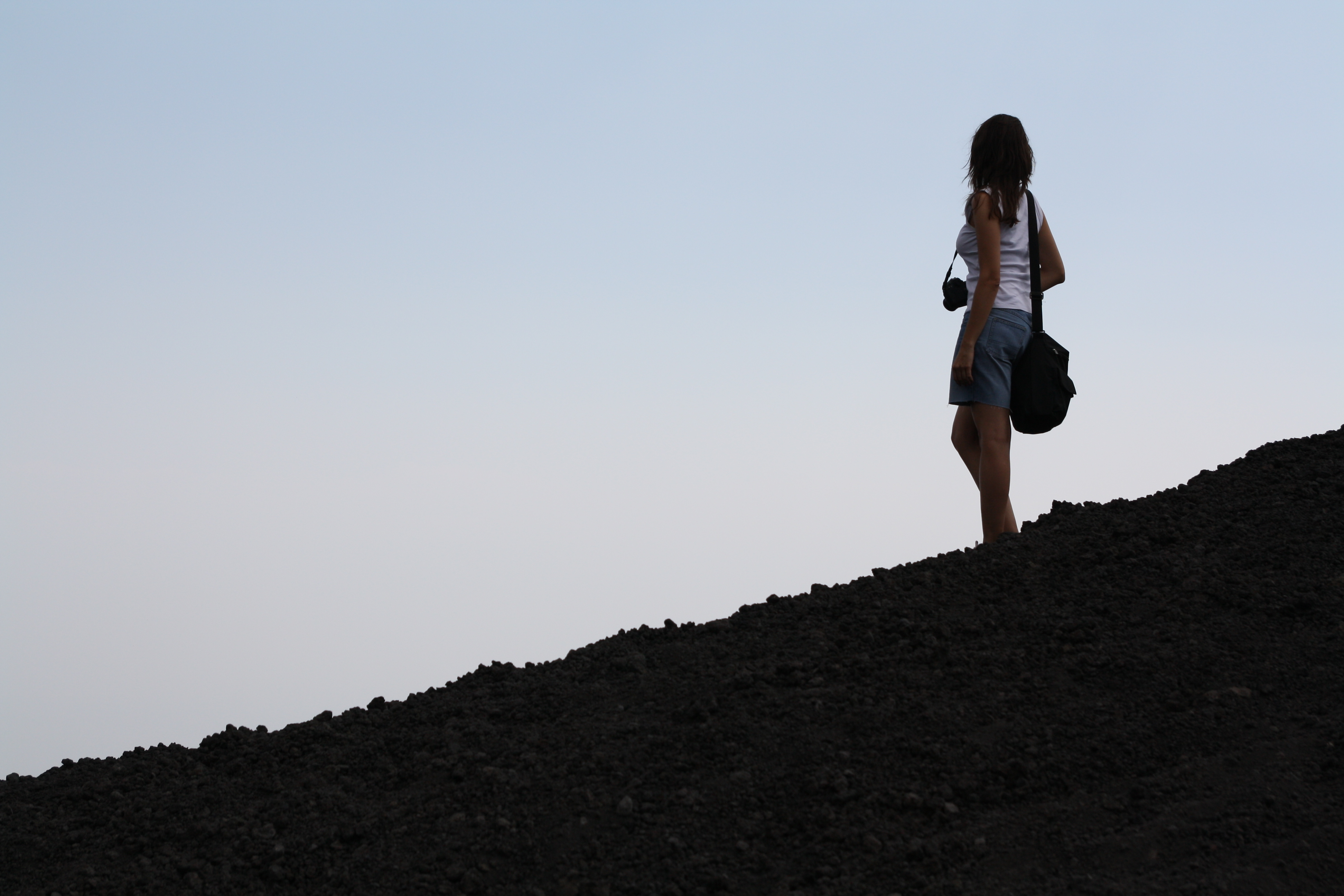 A photo of a girl standing against a pale blue sky, on the Mount Etna, in Sicily, Italy