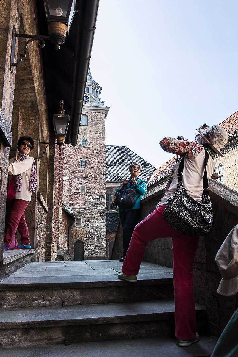 Asian tourists posing in the courtyard of the Akershus Fortress, Oslo.